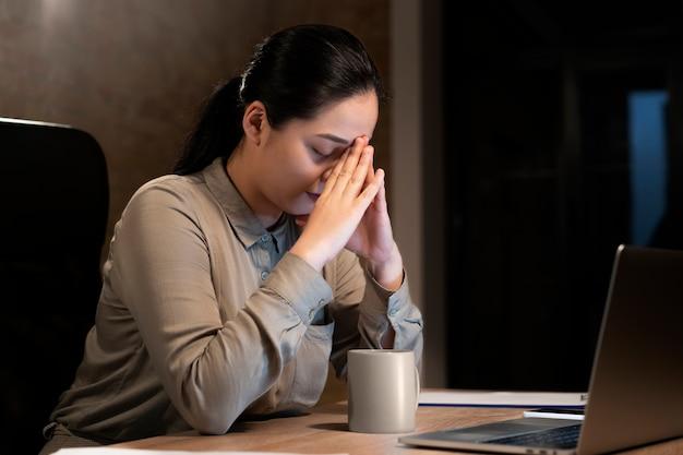 Mujer cansada trabajando hasta tarde para un proyecto