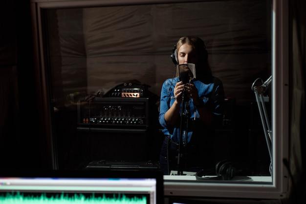 Mujer cantando un canto con el teléfono móvil en el estudio de grabación. usted
