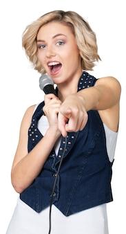Mujer cantando en micrófono aislado sobre fondo blanco.
