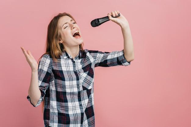 Mujer cantando en el micrófono con espacio de copia