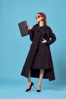 Mujer en una capa negra con una maleta sobre un fondo azul.