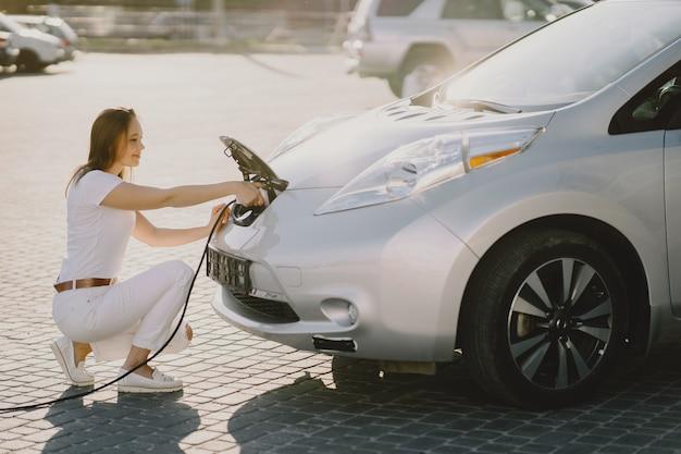 Mujer carga electro car en la gasolinera eléctrica