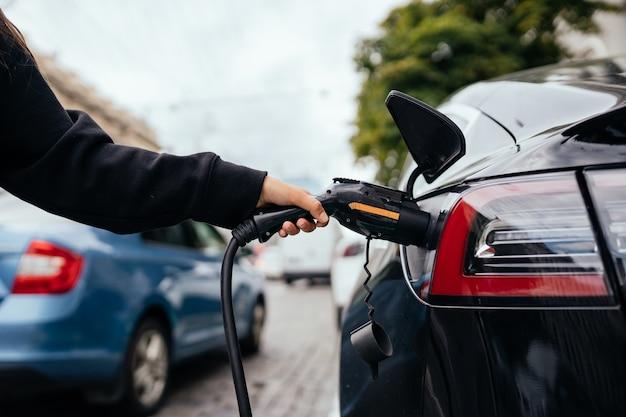 Mujer cargando coche eléctrico en la estación de carga.