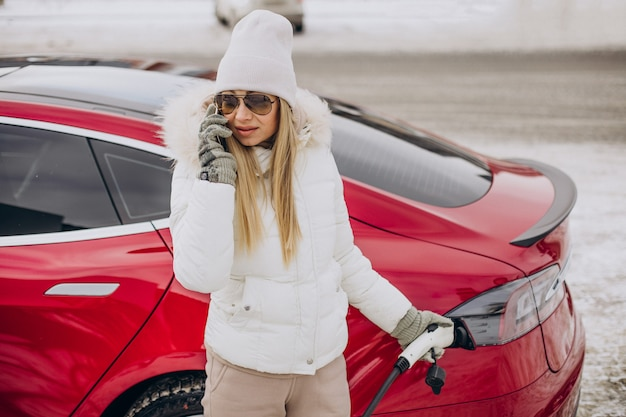 Mujer cargando coche eléctrico rojo, en época de invierno