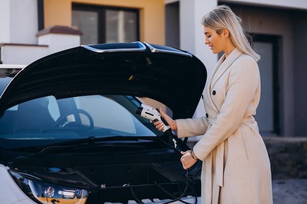 Mujer cargando electro car por su casa y sosteniendo el cargador
