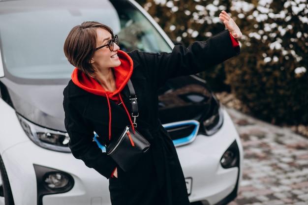 Mujer cargando electro car por su casa