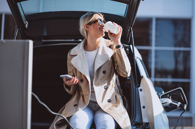 Mujer cargando electro coche en la gasolinera eléctrica