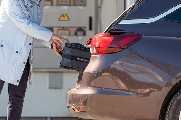 Mujer cargando la maleta en el baúl del auto