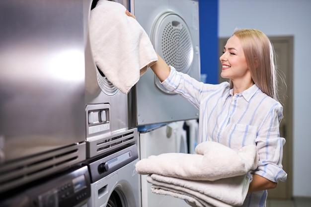 Mujer cargando toallas de lino en la lavadora, mujer caucásica joven va a utilizar la lavadora rápida moderna