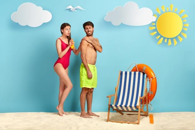 Mujer cariñosa aplica crema de protección solar en el hombro del marido, pone crema solar en la piel, párese en la cálida arena de la playa