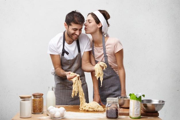 Mujer cariñosa va a besar a marido trabajador que hace masa y la ayuda en la cocina