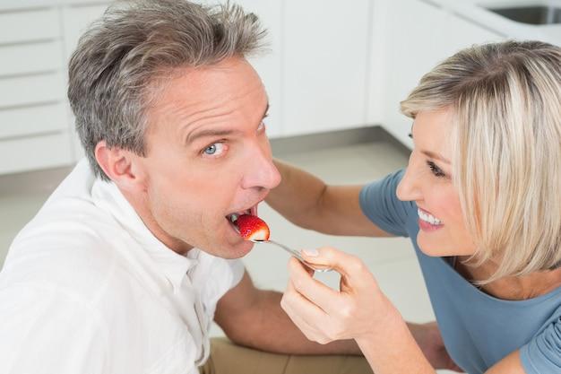 Mujer cariñosa que alimenta al hombre en la cocina