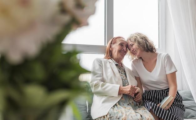 Mujer cariñosa con su abuela sentada en el sofá en casa