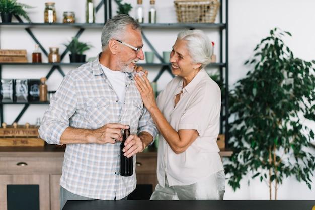 Mujer cariñosa con su marido abriendo la botella de cerveza en la cocina