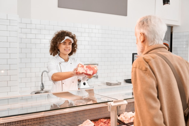 Mujer carnicero demostrando carne al anciano.