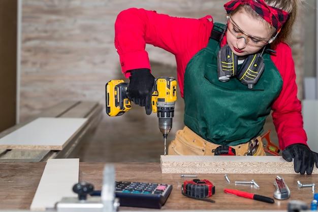 Mujer carpintero haciendo agujero en la plancha de madera.