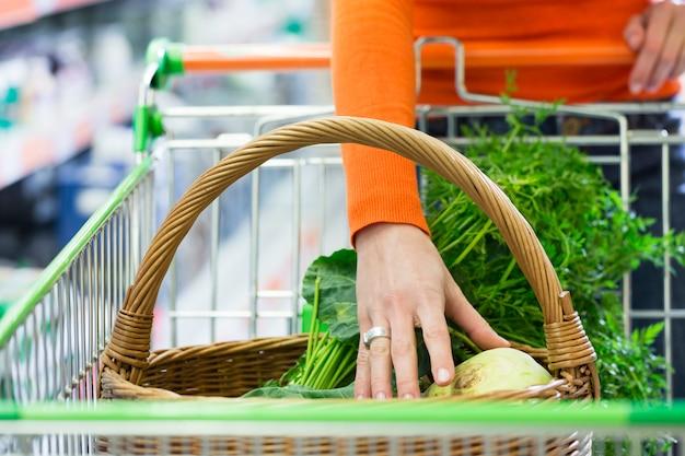 Mujer con carrito de compras en supermercado