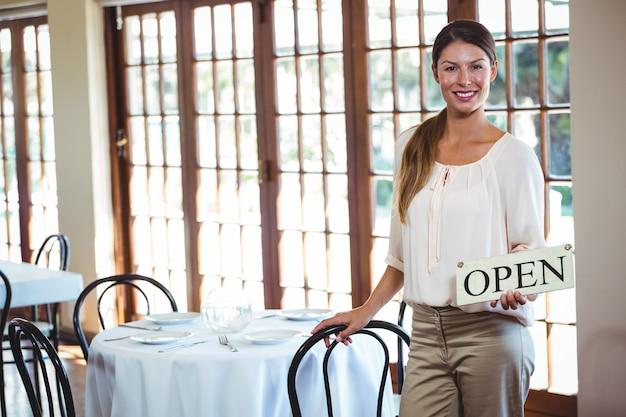 Mujer con un cartel con abierto