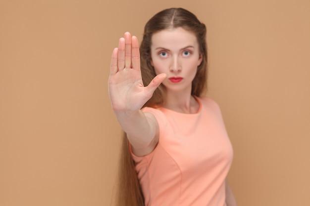 Para. mujer con cartel de prohibición mirando a la cámara. retrato de mujer hermosa, linda emocional con maquillaje y cabello largo en vestido rosa. interior, tiro del estudio, aislado en fondo marrón claro o beige.
