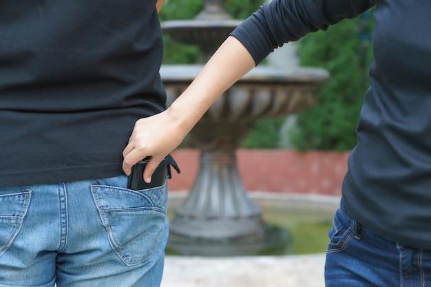 Mujer carterista robando una billetera por detrás del bolsillo en jeans en el parque