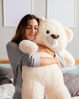 Mujer en casa abrazando gran oso de peluche