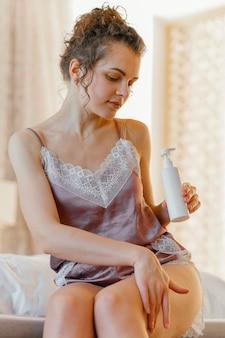 Mujer en casa aplicando loción