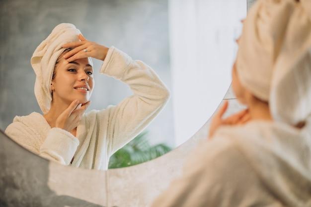 Mujer en casa aplicando mascarilla crema