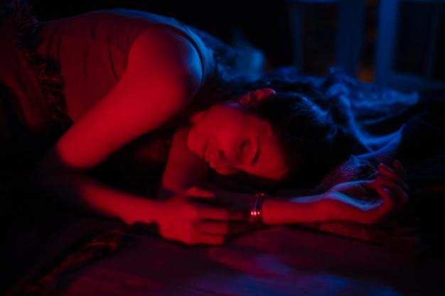 Mujer en casa con misteriosas luces de dormitorio