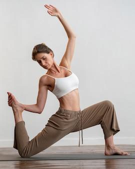 Mujer en casa practicando yoga en mat