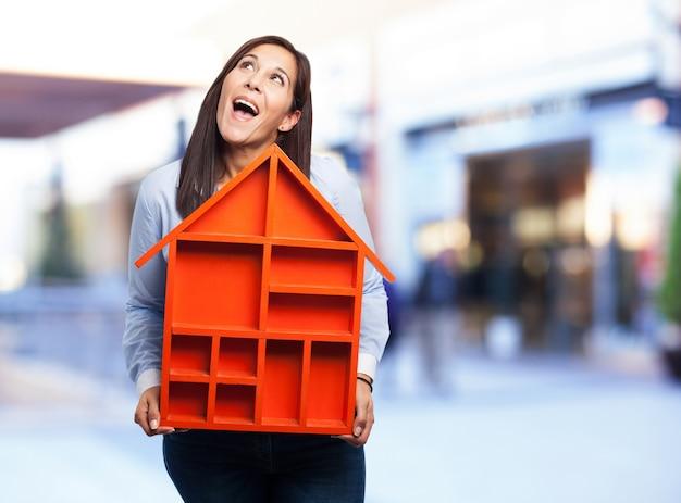 Mujer con una casa roja pequeña