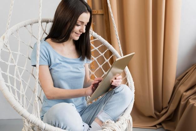 Mujer en casa sosteniendo y mirando portátil