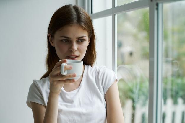 Mujer en casa con una taza de bebida cerca de la ventana vista pensativa