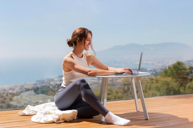 Mujer, en casa, usar la computadora portátil