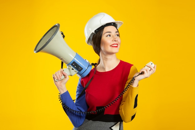Mujer en casco de construcción y altavoz en manos