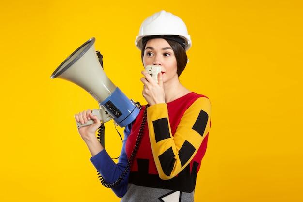 Mujer en casco de construcción con altavoz