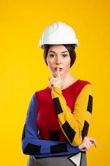 Mujer en casco de construcción muestra silencio