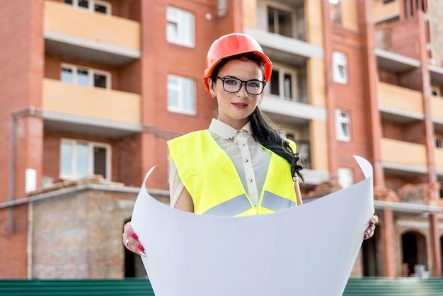 Mujer en casco mirando el dibujo en el sitio de construcción