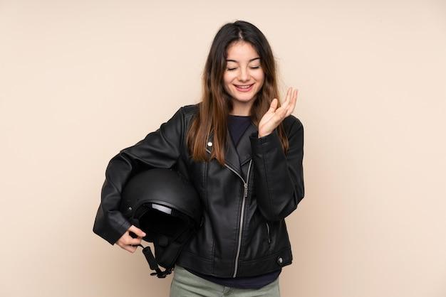 Mujer con casco de moto en pared beige infeliz y frustrada con algo