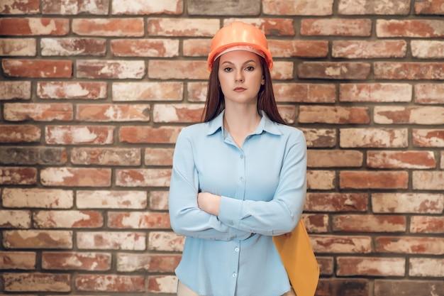 Mujer en casco protector con los brazos cruzados.