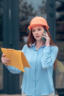Mujer en casco protector comunicándose por teléfono inteligente