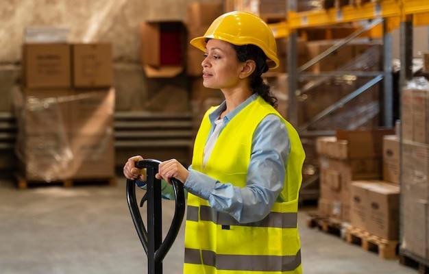 Mujer con casco trabajando en almacén