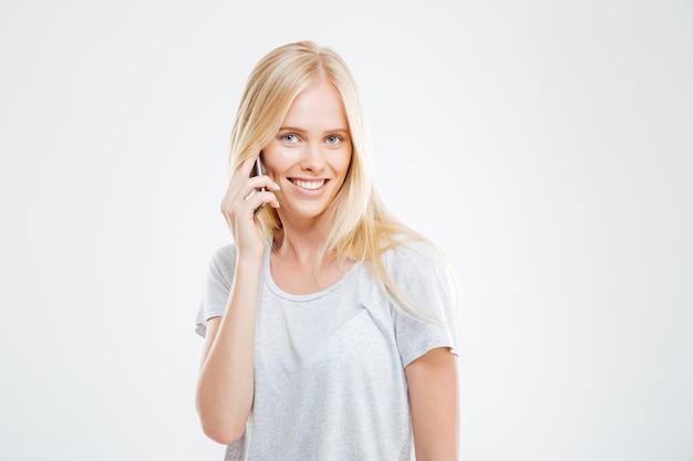 Mujer casual alegre hablando por teléfono aislado en una pared blanca