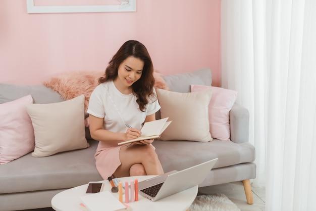 Mujer casual asiática joven que trabaja en línea de la pequeña empresa empaquetando su cheque el artículo en un cuaderno y tomando notas. concepto de propietario de pequeña empresa venta en línea, concepto de comercio electrónico