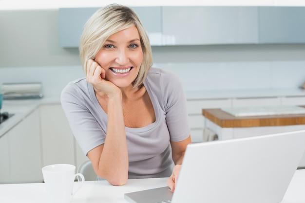 Mujer casual con café y laptop en cocina