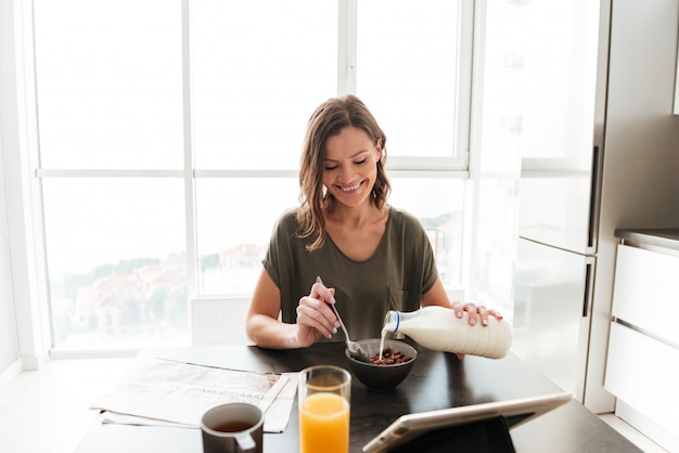 Mujer casual contenta comiendo junto a la mesa en la cocina y mirando la tableta