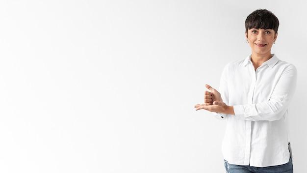 Mujer casual enseñando lenguaje de señas con espacio de copia
