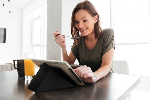 Mujer casual feliz comiendo junto a la mesa en la cocina y mirando la tableta