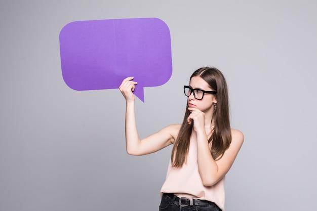 Mujer casual que sostiene el bocadillo de diálogo aislado en la pared blanca