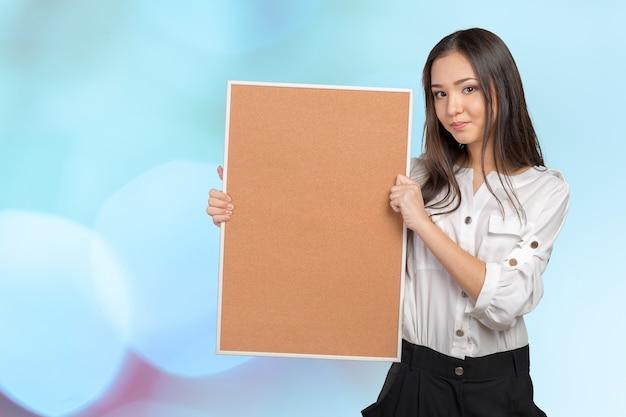 Mujer casual sonriente que sostiene el panel de corcho vacío