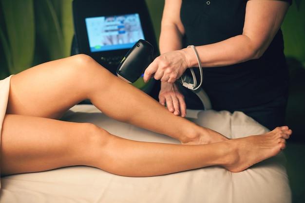 Mujer caucásica acostada en una clínica de spa con procedimientos de depilación láser de piernas con un nuevo aparato
